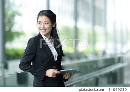 Successful chinese businesswoman using tablet iPad along office promenade 14049259