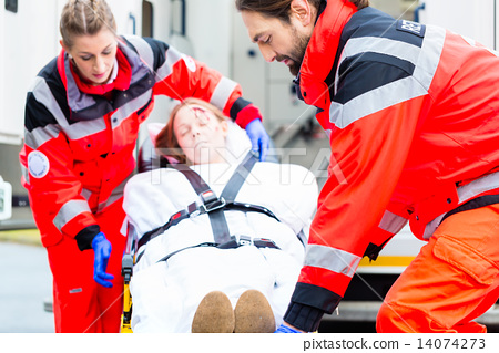 Stock Photo: Ambulance helping injured woman on stretcher
