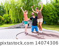 Family playing miniature golf outdoors 14074306