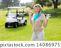 Cheerful golfer standing on the putting green 14086975