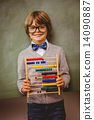 Boy holding abacus in front of blackboard 14090887