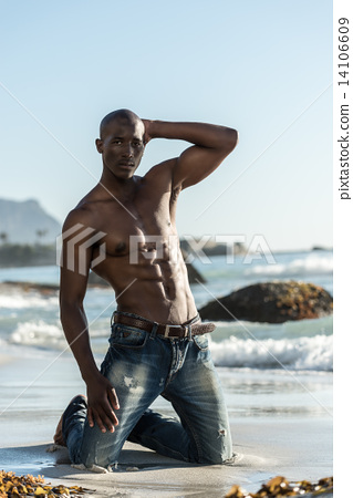African black man model with six pack topless, kneeling down during sunset at the beach 14106609