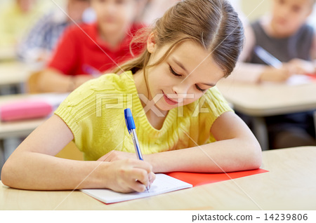 Stock Photo: group of school kids writing test in classroom