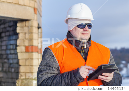 Worker with tablet PC near unfinished building  14403134