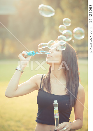 young beautiful brunette straight hair woman blowing soap bubble 14425068