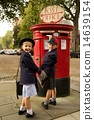 Schoolboy and sister smiling while posting letter 14639154
