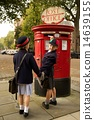Schoolboy turning while posting letter with sister 14639155