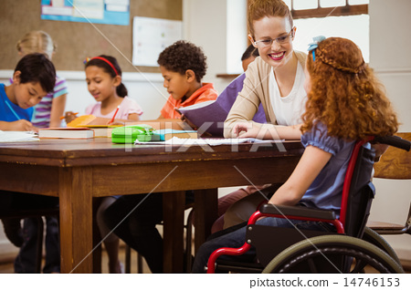 Stock Photo: Teacher helping a disabled pupil