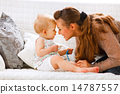 Cute baby with soother and young mom playing on divan 14787557