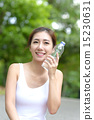 Young Chinese woman hydrating after exercising 15230631