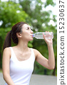 Young Chinese woman hydrating after exercising 15230637