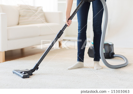 Stock Photo: close up of woman legs with vacuum cleaner at home