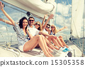 smiling friends sitting on yacht deck and greeting 15305358