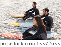 Group of friends on wetsuits with a surfboard on a sunny day 15572655