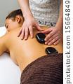 Massage therapist placing the hot stones 15664849