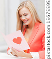 woman holding postcard with heart shape 15675595