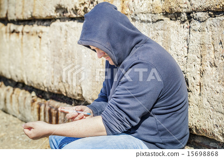 Drug addict man with syringe near hand at outdoor  15698868