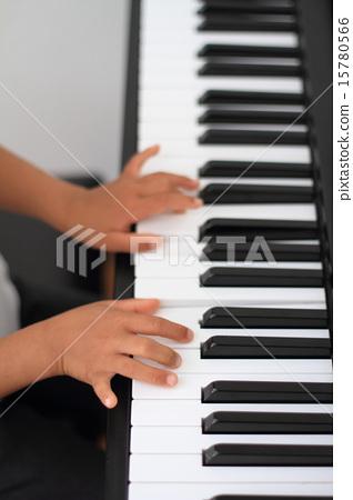 Children's hand playing the piano 15780566