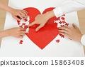 붉은 심장의 퍼즐을 만들어 인간의 손 15863408