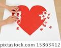 붉은 심장의 퍼즐을 만들어 인간의 손 15863412