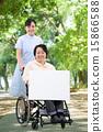พยาบาลหญิงคนหนึ่งกำลังเดินอยู่ในสวนพร้อมรถเข็นและหญิงวัยกลางคน 15866588