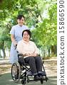 พยาบาลหญิงคนหนึ่งกำลังเดินอยู่ในสวนพร้อมรถเข็นและหญิงวัยกลางคน 15866590