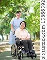 พยาบาลหญิงคนหนึ่งกำลังเดินอยู่ในสวนพร้อมรถเข็นและหญิงวัยกลางคน 15866592