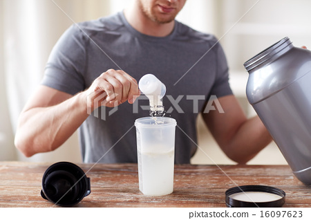 close up of man with protein shake bottle and jar 16097623