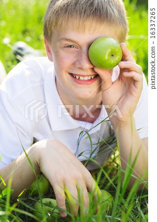 Teen boy is holding green apple near face 16337265