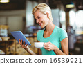 Pretty blonde having a coffee using tablet pc 16539921