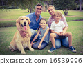 Happy family smiling at the camera with their dog 16539996