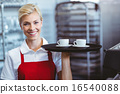 Pretty barista holding two cups of coffee 16540088