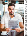 Young man having cup of coffee reading newspaper 16540152