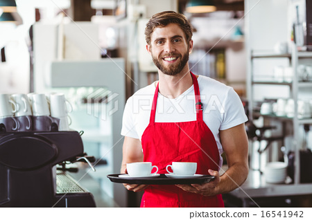 Stock Photo: Handsome barista holding two cups of coffee