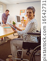 Creative businesswoman in wheelchair using a tablet 16542731