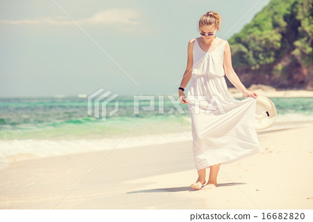 Young woman in long white dress holding hat walks along tropical beach having great summer time on 16682820