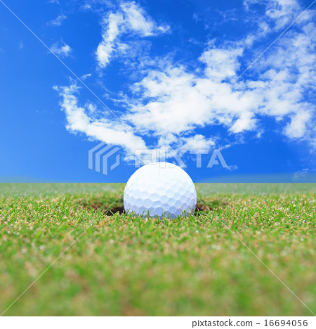 golf ball on lip of cup  16694056
