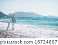 Mother walking with baby on seashore 16724897