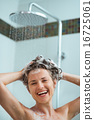Happy woman applying shampoo in shower 16725061