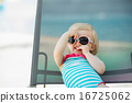 Portrait of baby in swimsuit and sunglasses laying on sunbed 16725062