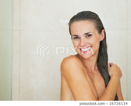 Portrait of happy young woman in shower 16726134