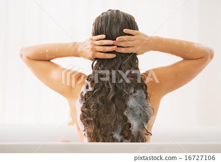 Stock Photo: Young woman washing hair. rear view