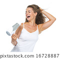 Smiling young woman singing while blow-dry 16728887