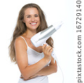 Portrait of smiling young woman with hairdryer 16729140