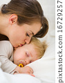 Closeup on mother kissing sleeping baby 16729257