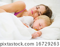 Baby and mother sleeping together in bed 16729263