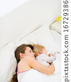 Mother sleeping with baby in bed 16729386