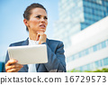 Portrait of thoughtful business woman in front of office buildin 16729573