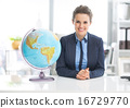 Portrait of happy business woman near earth globe 16729770