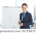 Portrait of smiling business woman near flipchart 16729875